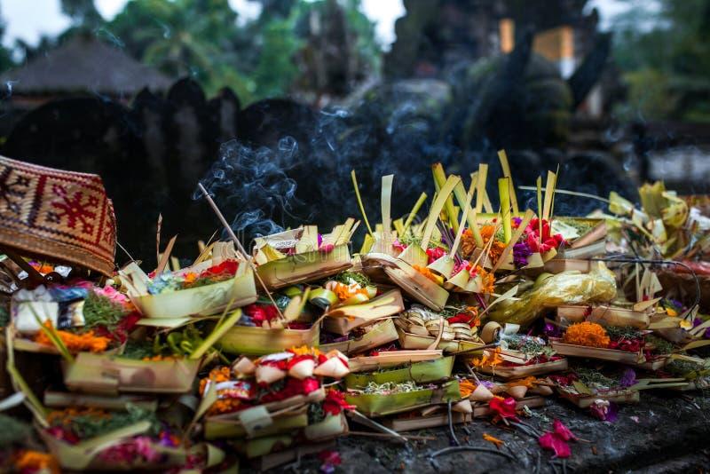 Traditionella balineseofferings till gudar i Bali med blommor och aromatiska pinnar Bali Indonesien, Tirta Empul tempel royaltyfria bilder