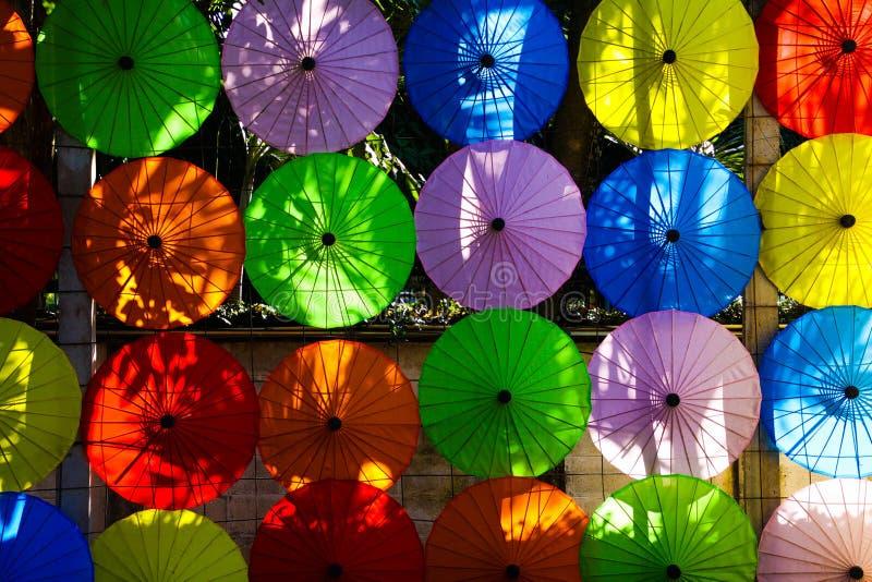 Traditionella färgrika pappers- paraplyer som i rad hänger på väggen i aftonsolen i Chiang Mai, Thailand royaltyfria bilder