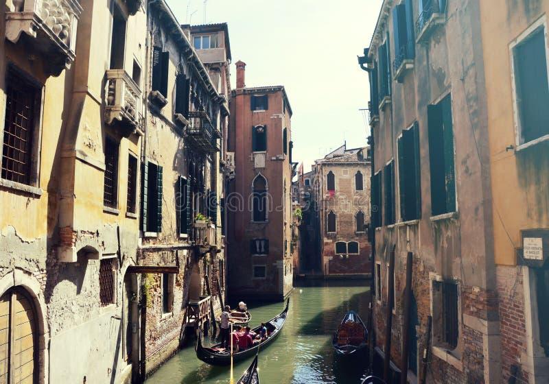 Traditionella gondoler på den smala kanalen mellan gamla slottar i Venedig, Italien Retro tappningfilter arkivfoton