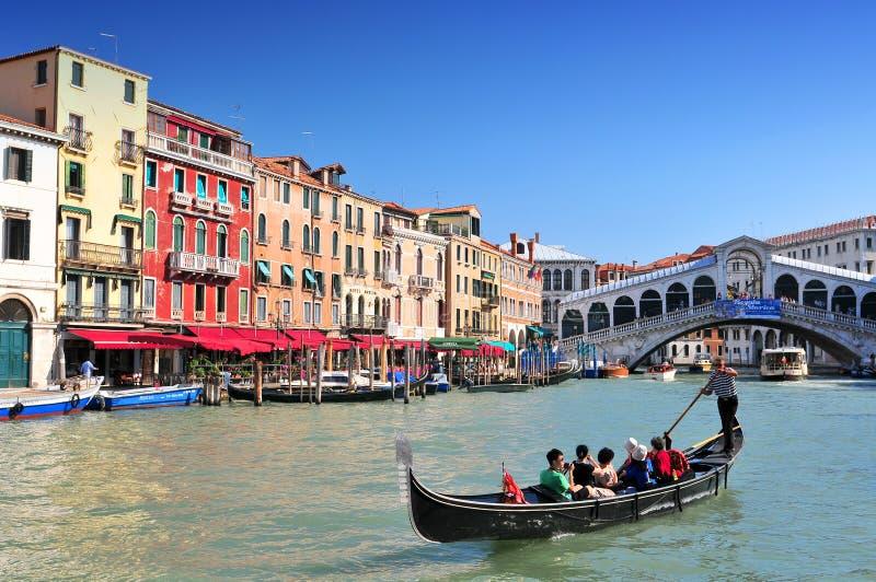 Traditionella gondoler på kanalen som är stor på den berömda Rialto bron Venedig Italien royaltyfria foton