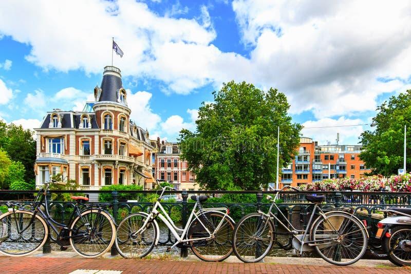 Traditionella holländarecyklar som parkeras längs gatan på Museumbrug broar över kanalen Amsterdam i sommar, Nederländerna, Europ arkivbilder