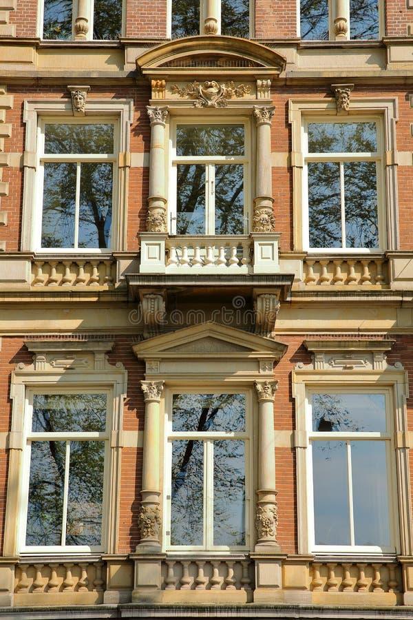 Traditionella holländska gamla fasader som lokaliseras på den Weesperzijde gatan längs den Amstel floden, Amsterdam royaltyfri fotografi