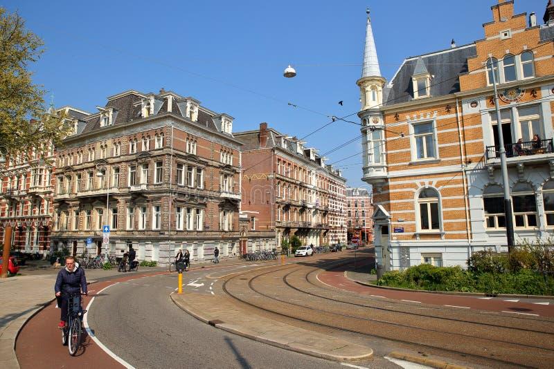 Traditionella holländska gamla fasader som lokaliseras på den Weesperzijde gatan längs den Amstel floden, med folk som cyklar i f royaltyfri foto