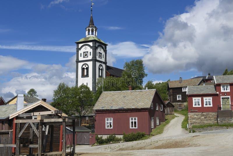 Traditionella hus och yttersida för torn för kyrklig klocka av kopparminstaden av Roros, Norge arkivbilder