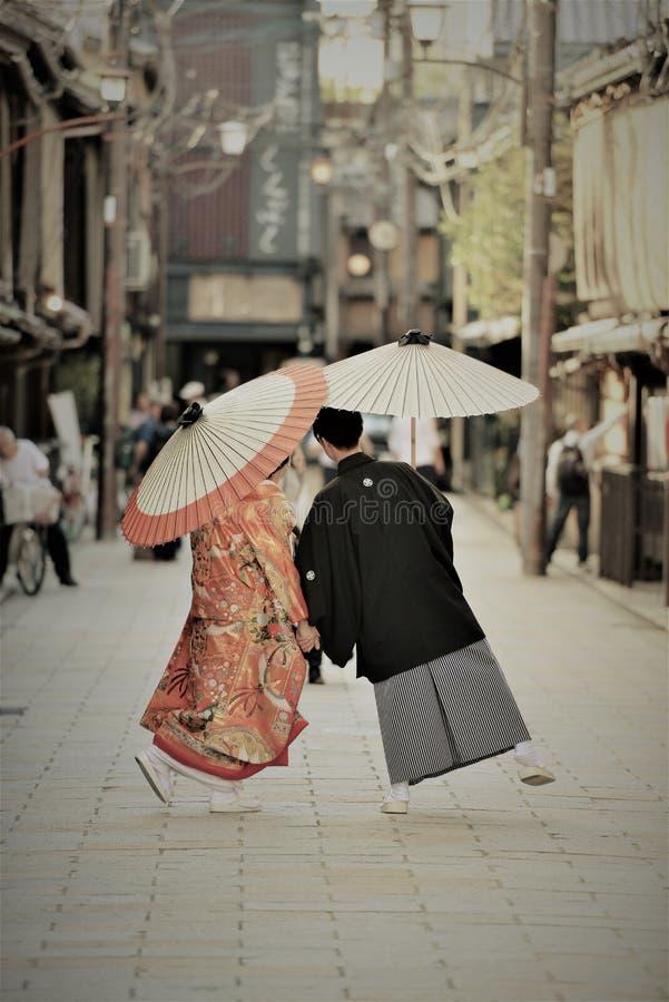 Traditionella japanska dräkter som är slitna vid ett ungt par på deras förbindelsedag royaltyfria bilder