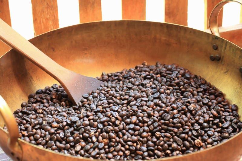 Traditionella kaffebönor som grillar i metallhandfat med spateln royaltyfri bild