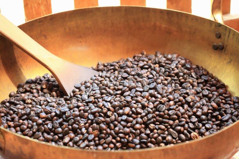 Traditionella kaffebönor som grillar i metallhandfat med spateln royaltyfri foto