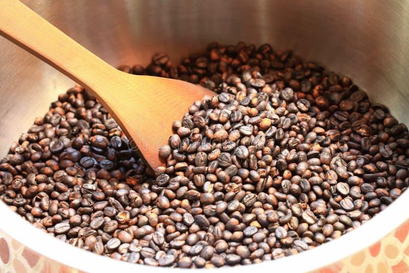 Traditionella kaffebönor som grillar i metallhandfat med spateln arkivfoto