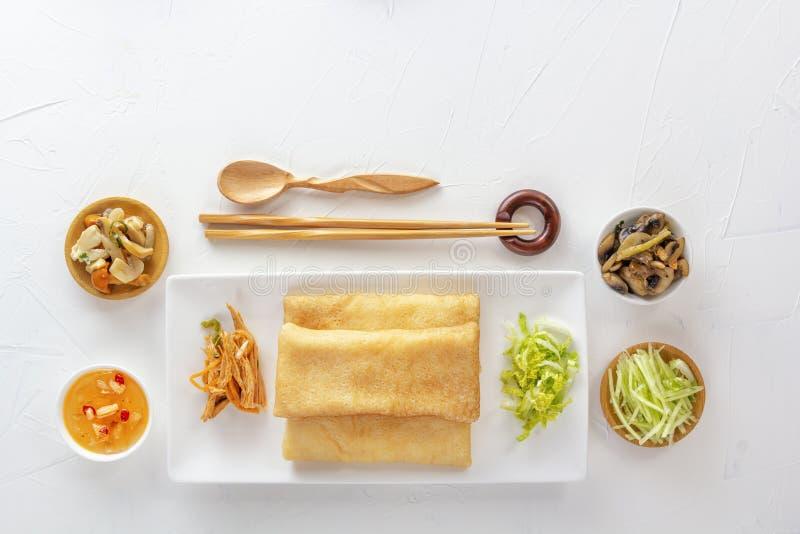 Traditionella kinesiska tortillor som fylls med bings i en platta på en vit bakgrund, varma sallader, fördämningSam mellanmål arkivfoto