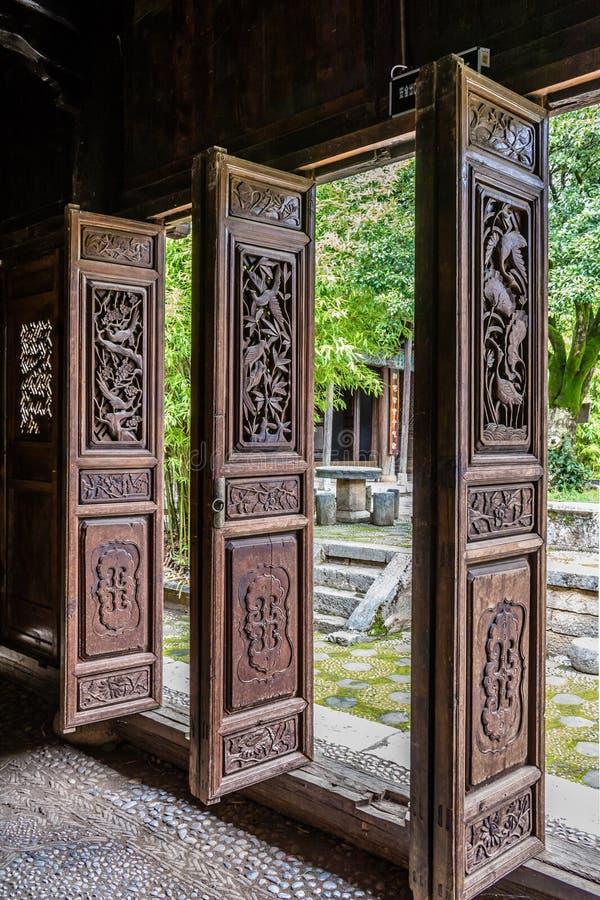 Traditionella kinesiska träsned dörrar öppnade på en borggård arkivfoton
