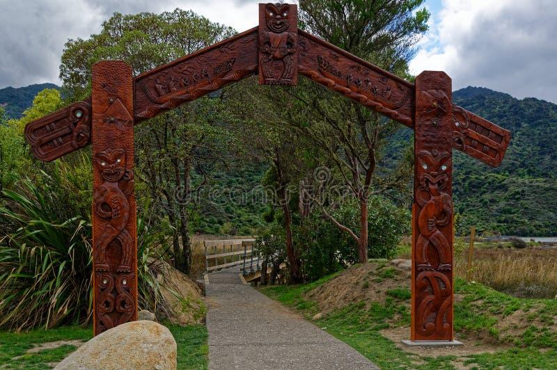Traditionella maoricarvings på ingången till Nyas Zeeland Abel Tasman National Park arkivfoto