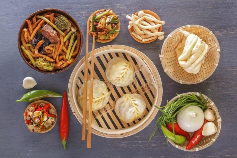 Traditionella mellanmål av den kinesiska kokkonstdim sum - klimpar, kryddiga sallader, grönsaker, nudlar, ångabröd royaltyfri bild