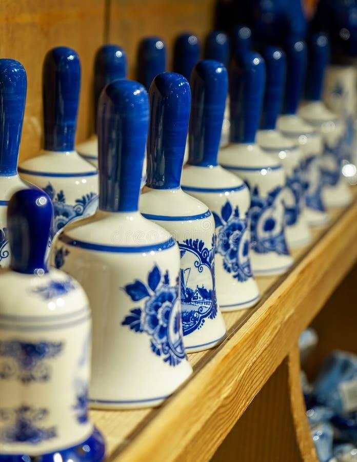 Traditionella netherlands vita för porslin keramiska och blåa handcrafted souvenirklockor på shops skärm arkivfoton