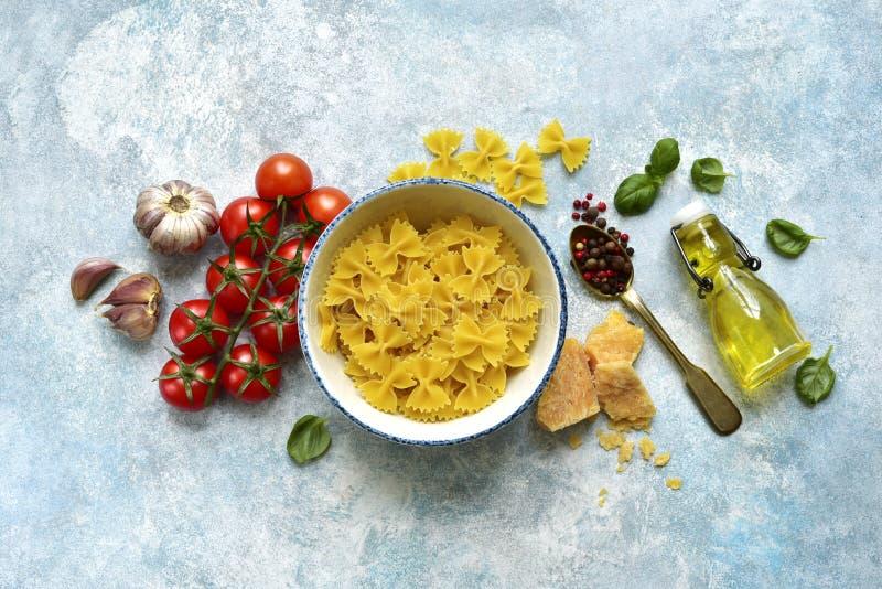 Traditionella organiska ingredienser av italiensk kokkonst: pasta, tomat, vitlök, olivolja, parmesanost och basilika Bästa sikt m royaltyfri foto