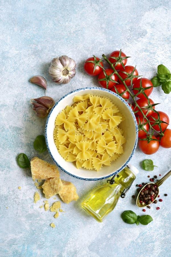 Traditionella organiska ingredienser av italiensk kokkonst: pasta, tomat, vitlök, olivolja, parmesanost och basilika Bästa sikt m arkivbilder