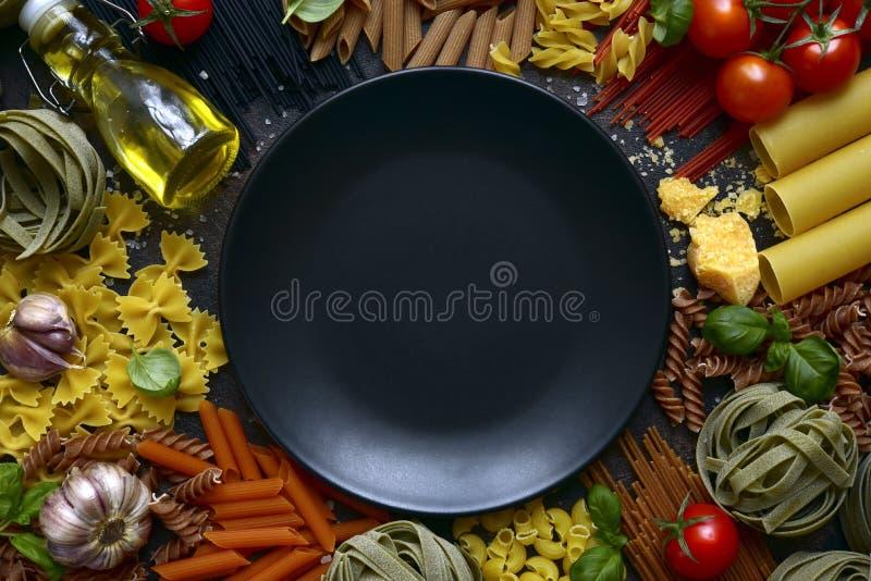 Traditionella organiska ingredienser i kursisk kokain: pasta, tomat, vitlök, olivolja, parmesanost och basilika med tom svart arkivfoton
