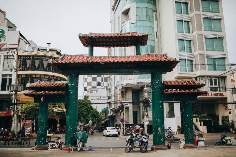 traditionella orientaliska portar och moderna byggnader på gatan av Ho Chi Minh, Vietnam royaltyfri foto