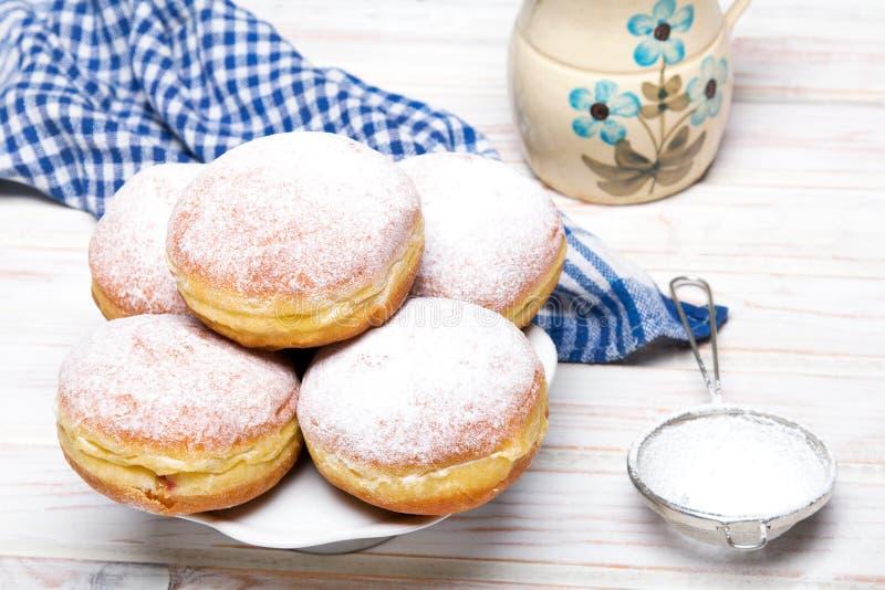 Traditionella polska donuts med pudrat socker på träbakgrund arkivbild