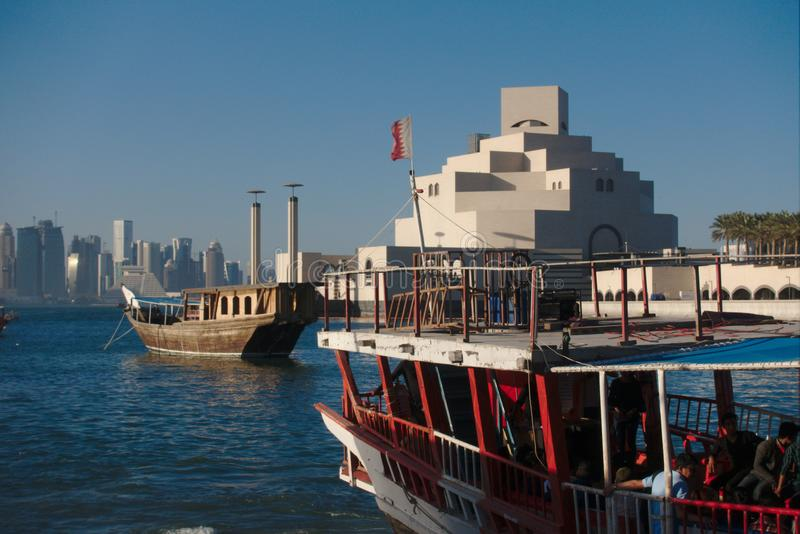 Traditionella qatariDhowfartyg med horisonten av västra fjärdskyskrapor som tas på solnedgången doha qatar royaltyfria foton