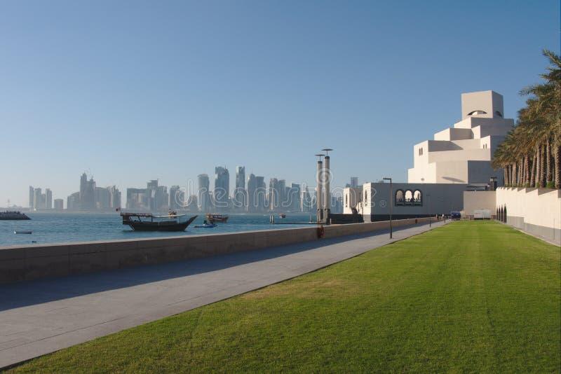 Traditionella qatariDhowfartyg med horisonten av västra fjärdskyskrapor som tas på solnedgången doha qatar royaltyfri bild