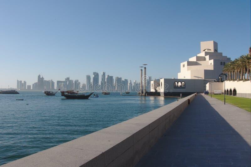 Traditionella qatariDhowfartyg med horisonten av västra fjärdskyskrapor som tas på solnedgången doha qatar arkivbilder