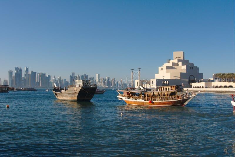 Traditionella qatariDhowfartyg med horisonten av västra fjärdskyskrapor som tas på solnedgången doha qatar fotografering för bildbyråer