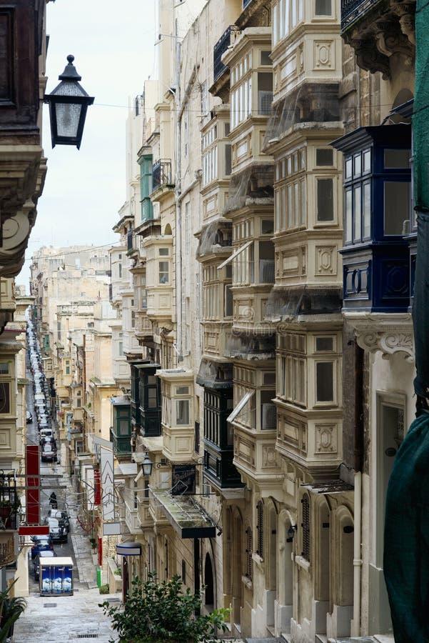 Traditionella smala gator med färgrika balkonger i Valletta arkivfoton