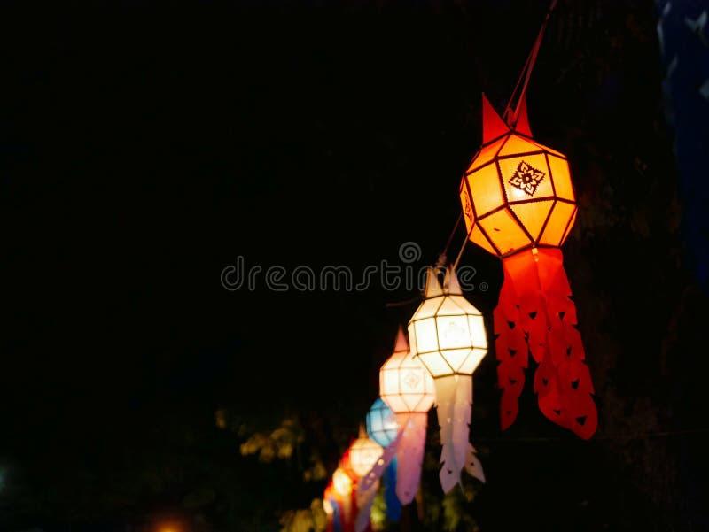 Traditionella thailändska Lanna som hänger pappers- lyktor som är van vid, dekorerar gatan under natten royaltyfri fotografi