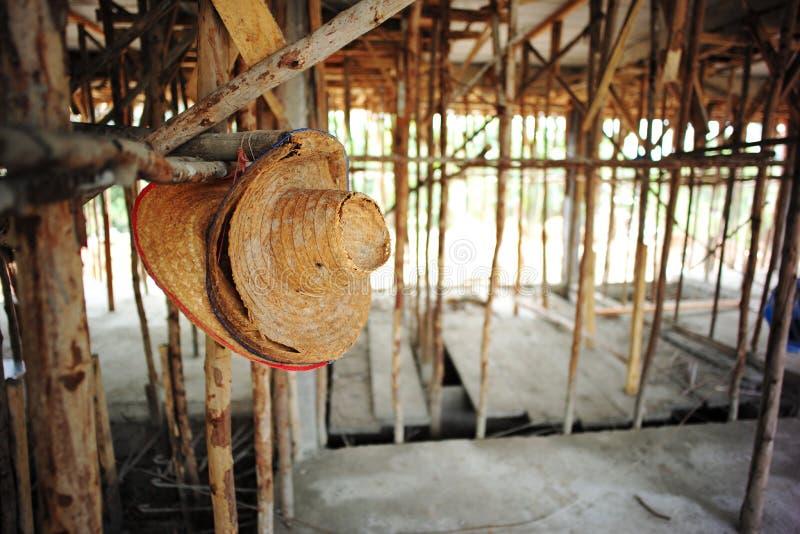 Traditionella väva hattar hänger på träpolen på konstruktionsplatsen arkivfoto