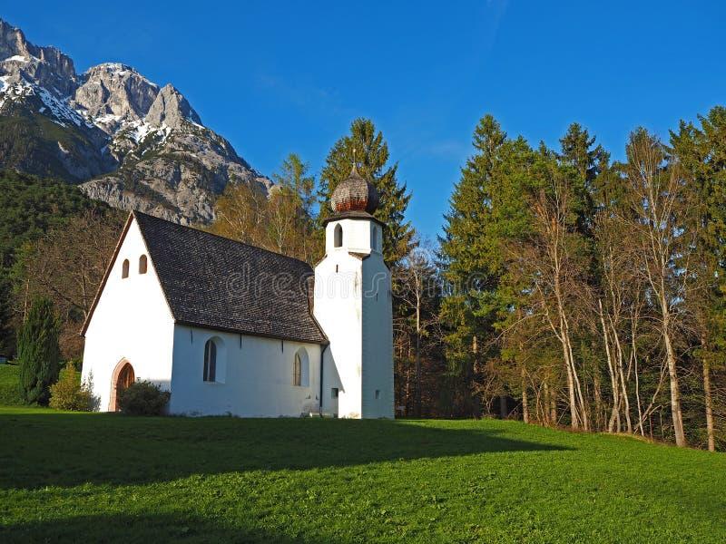 Traditionelle österreichische Kirche in der Gebirgsumwelt stockfotos