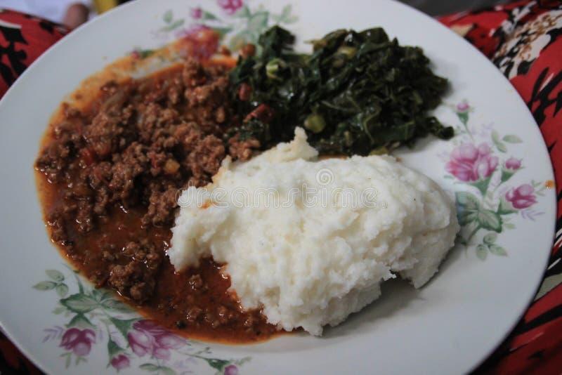 Traditionelle afrikanische Küche für arme Leute - Getreidemehlbrei Mais oder Ishim mit Spinat stockfotografie