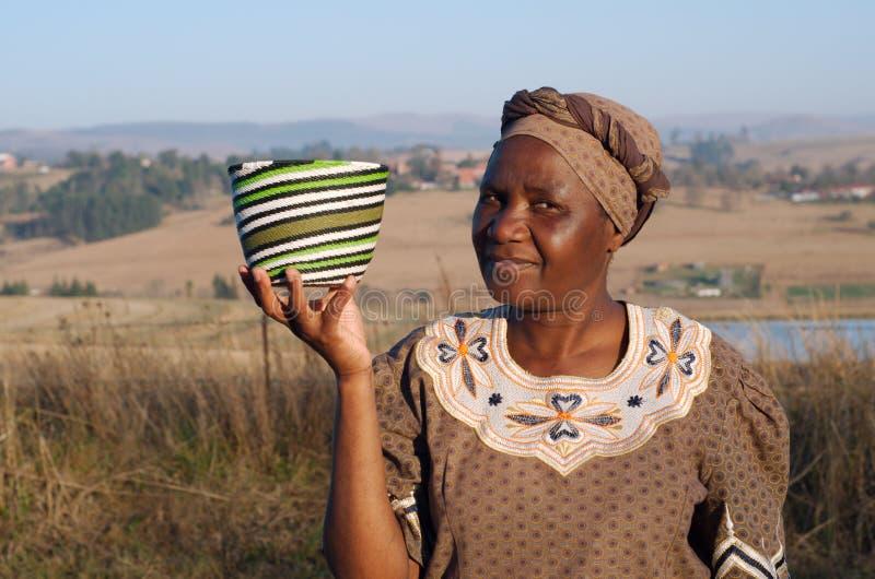 Traditionelle afrikanische Zulu- Frau, die Drahtkörbe verkauft stockfotografie