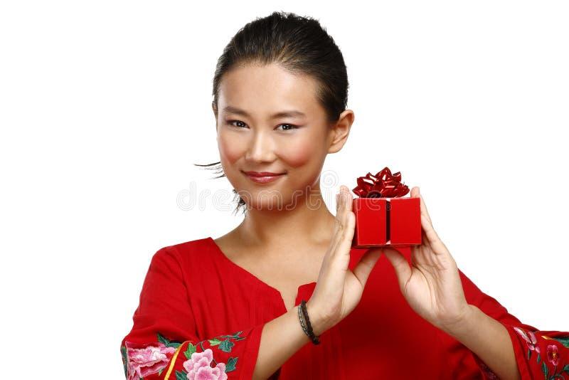 Traditionelle asiatische chinesische Frau mit einem Geschenk in ihren Händen stockfotografie