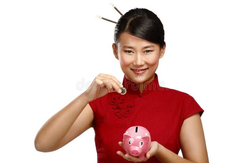 Traditionelle asiatische Frauenabwehr eine Münze in einem piggybank lizenzfreie stockfotografie