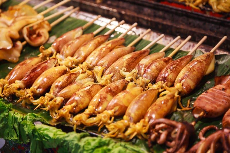 Traditionelle asiatische thailändische Straßennahrung und Schnellimbiß, köstlicher gegrillter Kalmar Calamari spießt im Nahrungsm stockfotografie