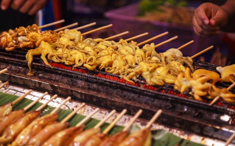 Traditionelle asiatische thailändische Straßennahrung und Schnellimbiß, köstlicher gegrillter Kalmar Calamari spießt im Nahrungsm lizenzfreie stockbilder