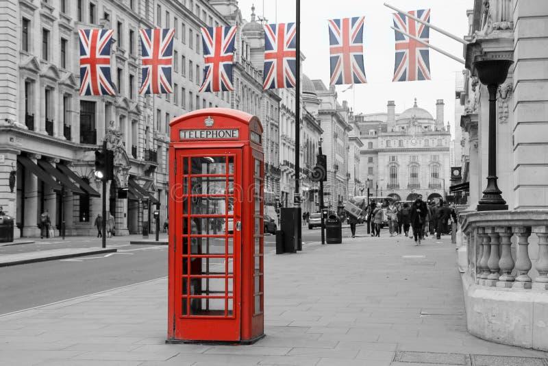 Traditionelle britische rote Telefonzelle mit Flaggen lizenzfreies stockfoto