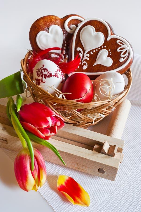 Traditionelle Dekoration Tschechen Ostern - selbst gemachte Lebkuchenherzen backt mit Tulpenblumen, gemalten Eiern und Ratsche zu stockbild