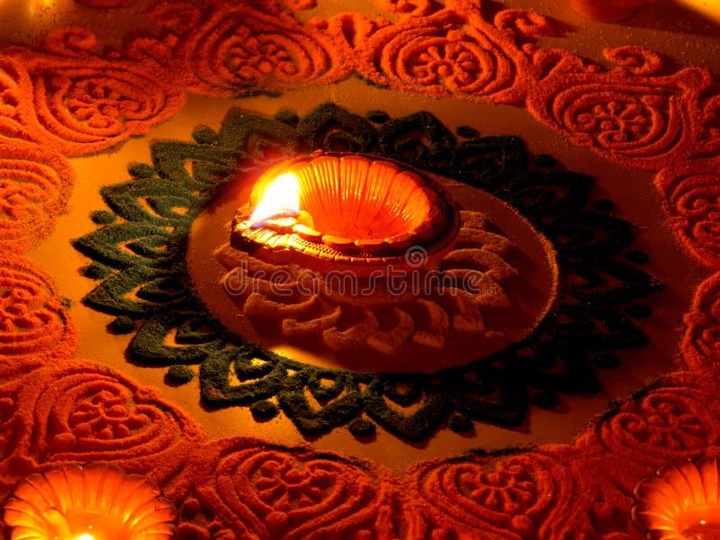 Traditionelle diya Lampe beleuchtet auf buntem rangoli stockfotos