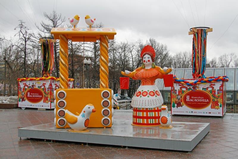 Traditionelle Dymkovo-Spielzeugfrau mit einem Joch und der Eimer einem Brunnen nahe und Vögel als Kunstgegenstand an russischem n lizenzfreie stockfotografie