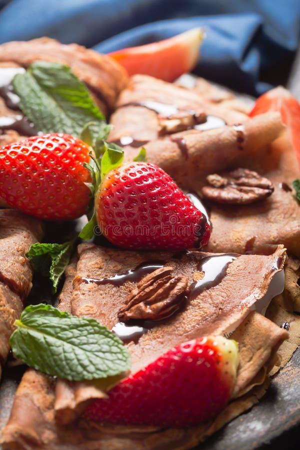 Traditionelle französische Krepps gekocht mit Schokolade Verziert mit Minze und Erdbeeren lizenzfreies stockbild