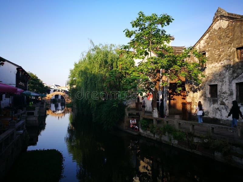 Traditionelle Gebäude, die über ruhigen Fluss nachdenken lizenzfreies stockfoto