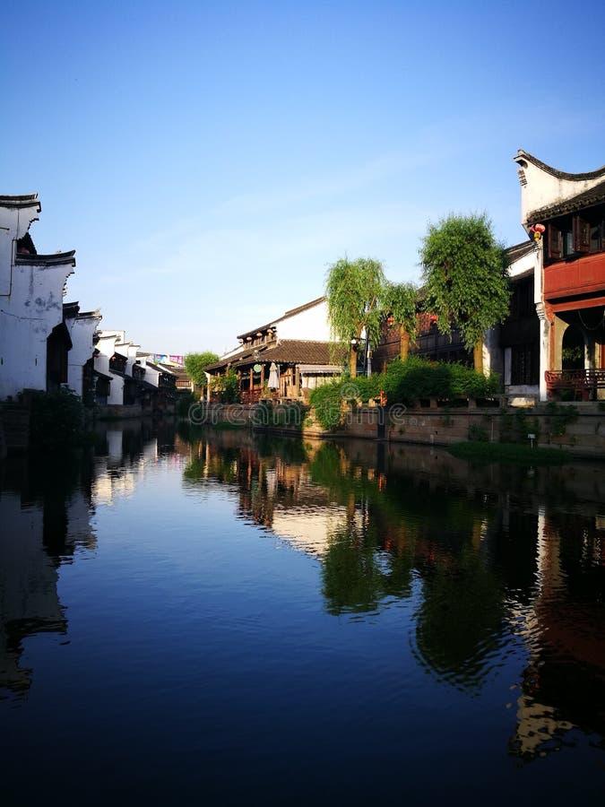 Traditionelle Gebäude, die über ruhigen Fluss nachdenken stockfotografie