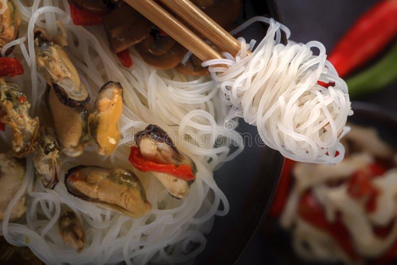 Traditionelle hölzerne Essstäbchen mit aufgerollten Reisnudeln auf dem Hintergrund eines Tellers mit Meeresfrüchten, Gemüse und P lizenzfreie stockbilder