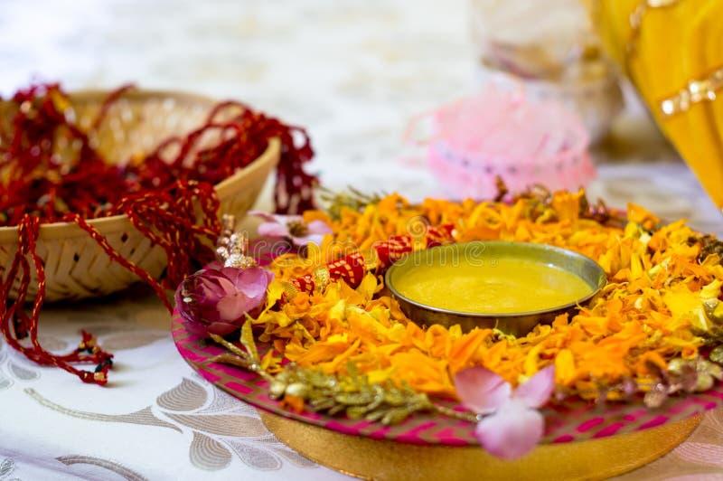 Traditionelle Haldi-Gelbwurz hielt auf einer Blumenplatte für die hindische Trauung stockbild