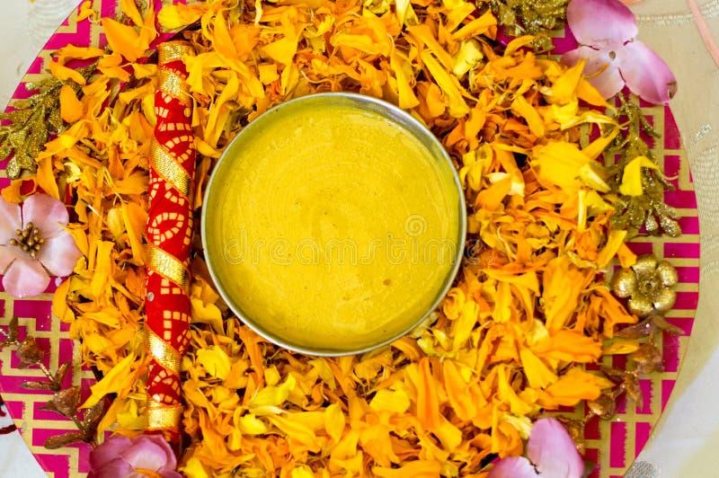 Traditionelle Haldi-Gelbwurz hielt auf einer Blumenplatte für die hindische Trauung lizenzfreie stockbilder