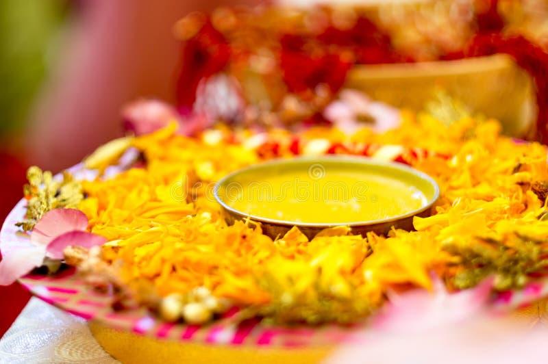 Traditionelle Haldi-Gelbwurz hielt auf einer Blumenplatte für die hindische Trauung lizenzfreies stockfoto