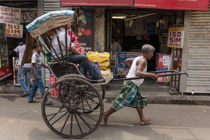 Traditionelle Hand zog den indischen Rikschafahrer, der an der Straße in Kolkata, Westbengalen, Indien arbeitet stockbild