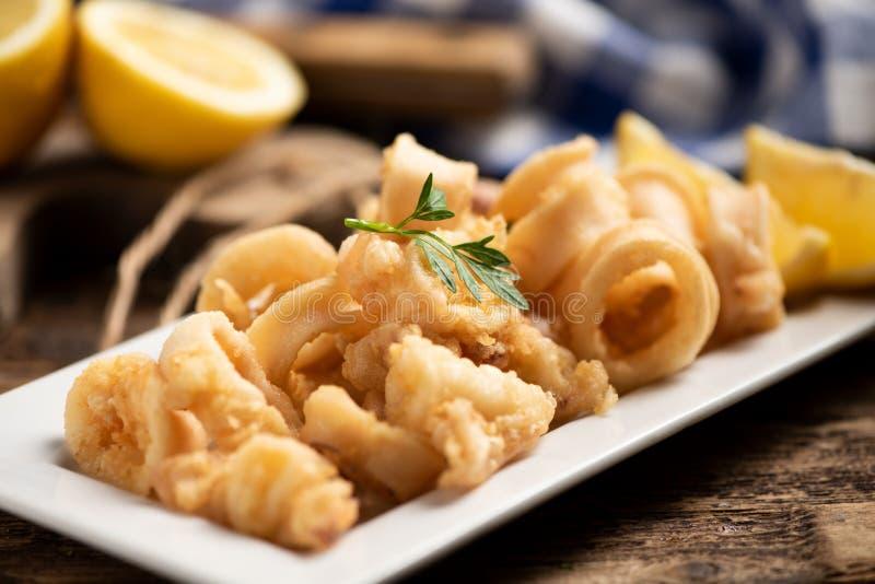 Traditionelle italienische gebratene Calamari- und Zitronenscheibe lizenzfreie stockfotos