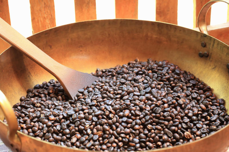 Traditionelle Kaffeebohnen, die im Metallbecken mit Spachtel braten lizenzfreies stockbild
